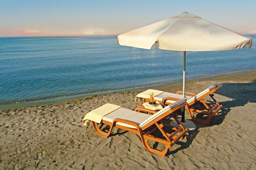 Ilmaiset pehmustetut aurinkotuolit sekä aurinkovarjot rannalla.