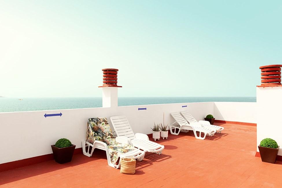Hotellin kattoterassilla on aurinkotuolit, ja hienot näkymät merelle päin